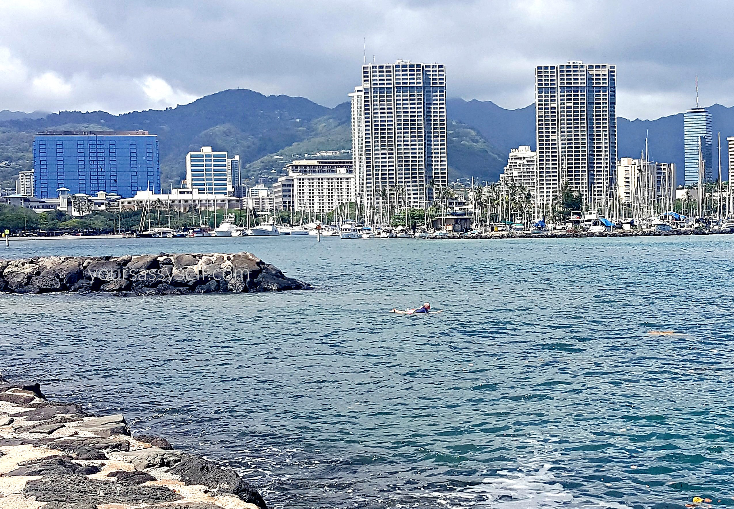 Surfer paddling in Waikiki waters - yoursassyself.com