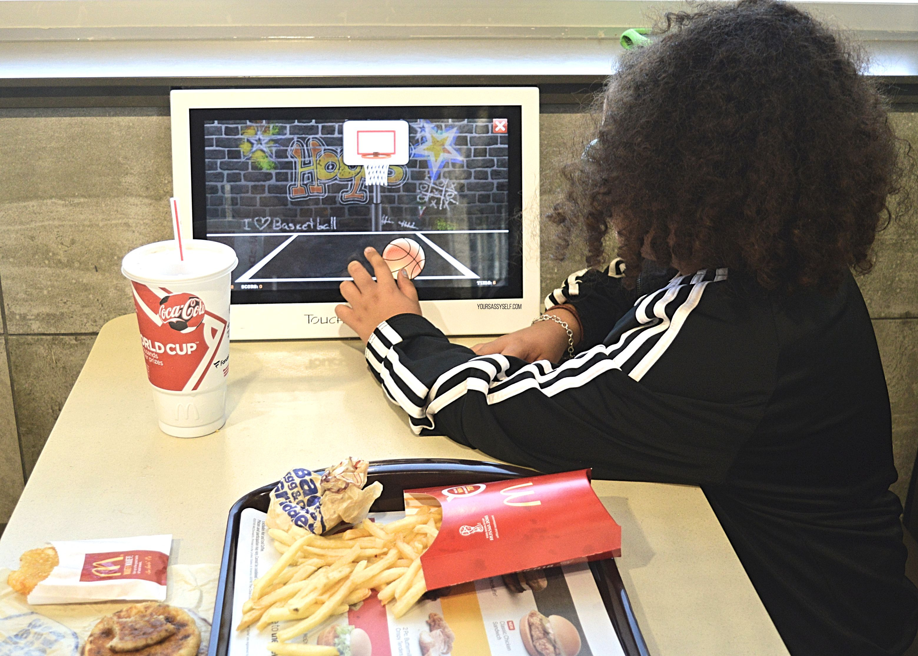 Girl playing on tablet at McDonald's - yoursassyself.com