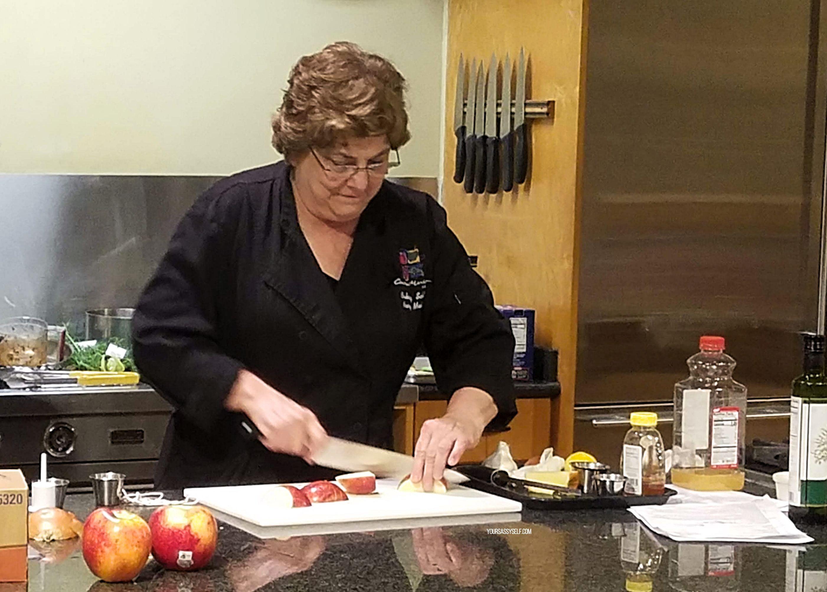 Chef cutting apple on cutting board - yoursassyself.com