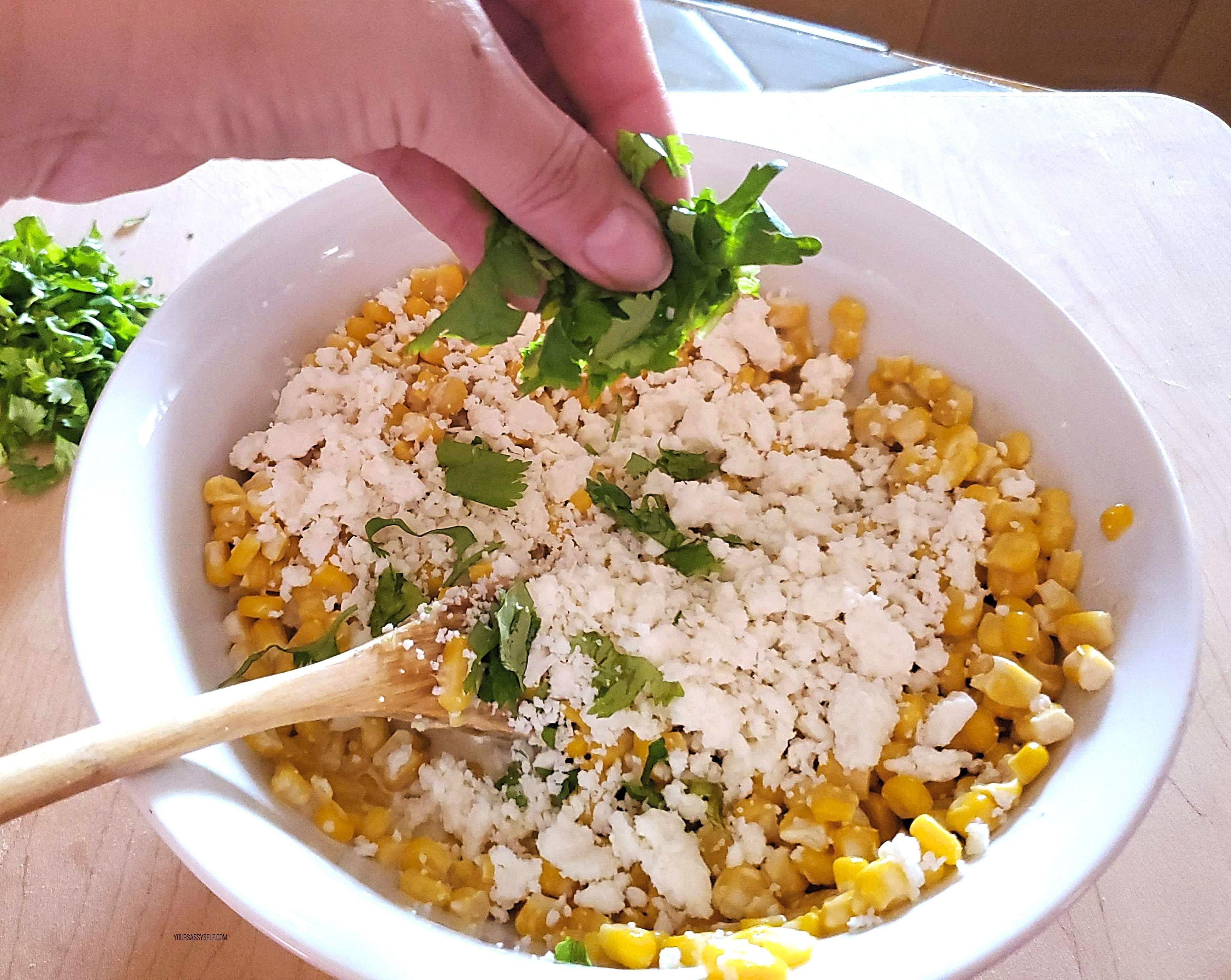 Adding cheese and cilantro to corn mixture - yoursassyself.com